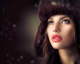 Beautiful-girl-wearing-a-brown-fur-hat-on-a-brown-background