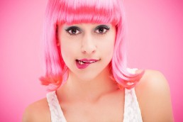 Beautiful-girl-with-pink-hair-biting-her-lip-in-front-of-a-pink-background