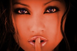 Closeup-of-beautiful-brunette-girl-with-brown-eyes-giving-a-shhh