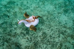 Girl-on-unicorn-pool-lounger-floating-in-the-shallow-sea