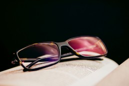 Set of eyeglasses resting on an open book with a black background