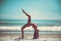 Woman in bikini performing gymnastics on the beach