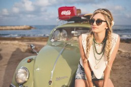 Women sitting on hood of green volkswagen bug whle parked on the beach