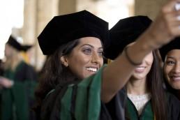 Young women at graduation ceremonies taking selfies