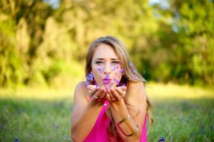Blonde girl sitting in green meadow and blowing a handful of purple flower petals from her cupped hands