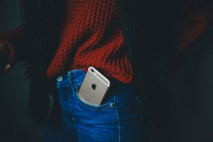 Woman with IPhone in the pocket of her blue jeans wearing a red sweater