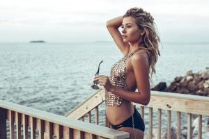 beautiful-girl-wearing-gold-halter-top-and-black-bikini-staring-out-at-the-ocean-view