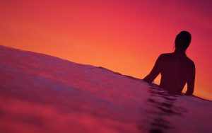 Surfer-Girl-waiting-for-a-wave-with-the-sun-setting-in-the-background